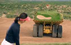 Caterpillar machines playing golf in the desert